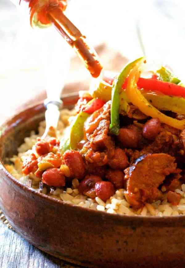 Red Beans and Rice with Chorizo and Bell Pepper Saute - Hot sauce being dripped onto dish