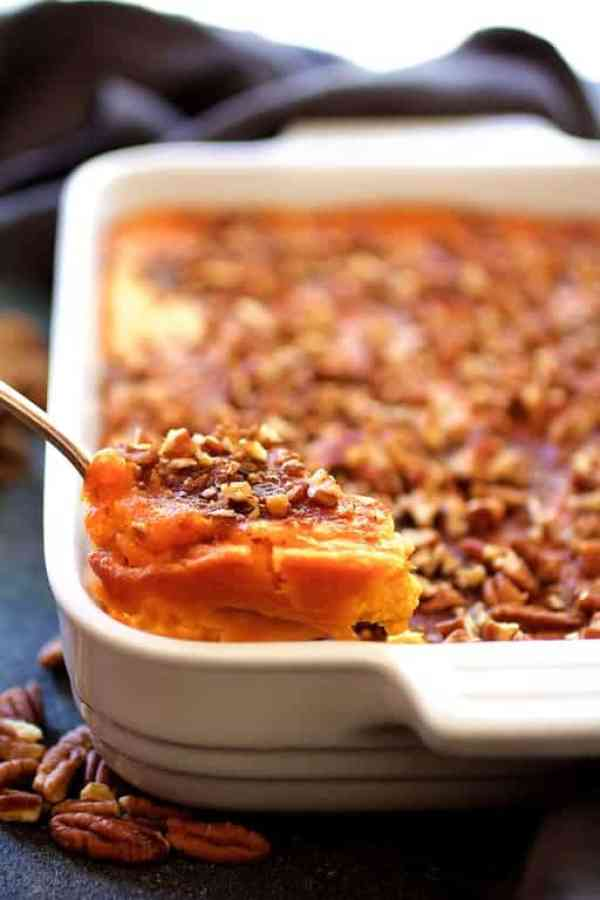 Jeannies Sweet Potato Souffle - Some of the sweet potato souffle being scooped out from white baking dish with silver serving spoon