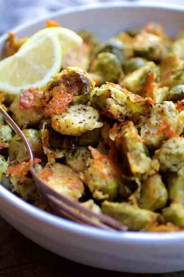 Lemon Parmesan Crusted Brussels Sprouts - Close-up shot in white bowl with serving spoon garnished with lemon wedges