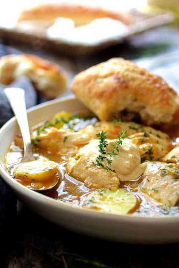 Chicken Bouillabaisse - Hero shot of dish in white bowl with bread resting on the side