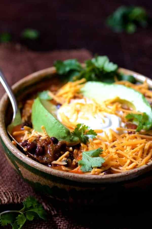 Straight-on shot of dish in Mexican-style bowl garnished with avocado, sour cream and cheese