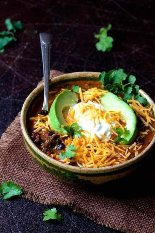 Beef and Chorizo Chili with Black Beans - Hero shot of dish on brown burlap garnished with avocado, sour cream, cheese and cilantro