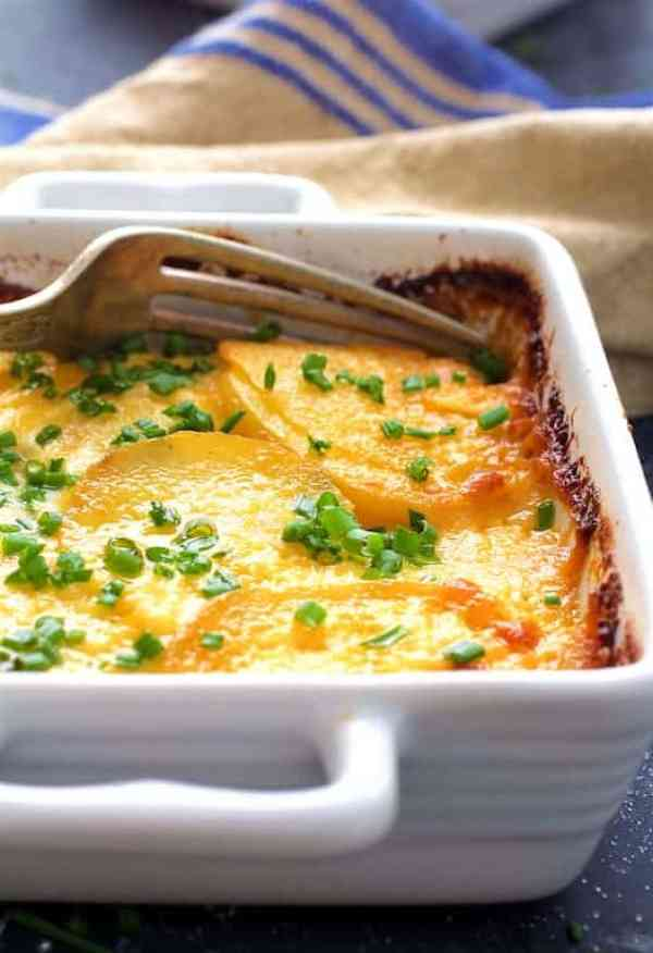 Au Gratin Potatoes for Two - Straight-on close-up shot with fork in white individual baking dish