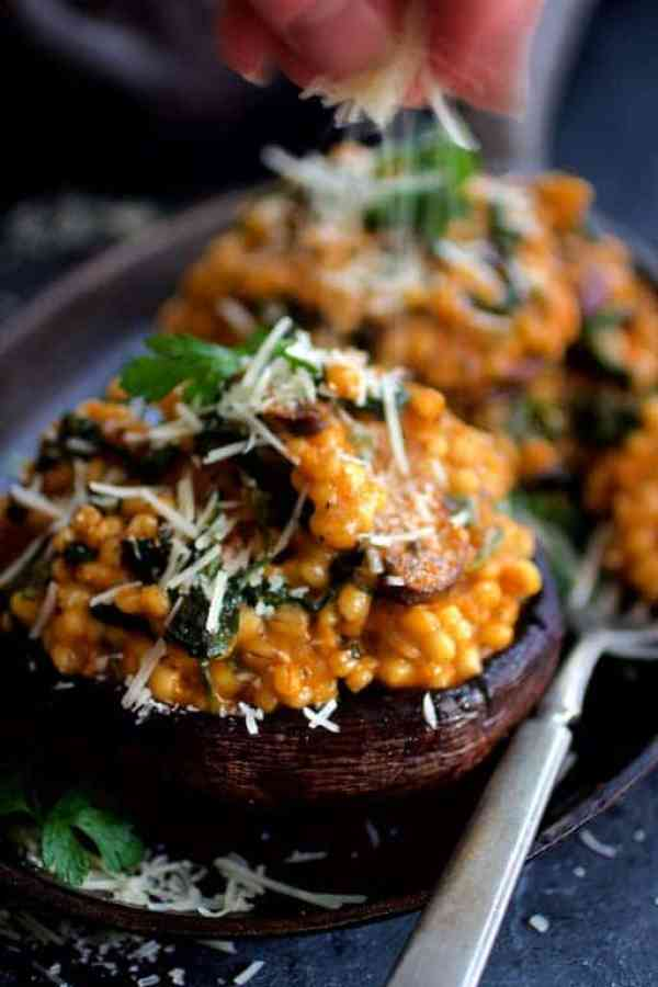 Barley Risotto Stuffed Portobello Mushrooms being sprinkled with Parmesan cheese