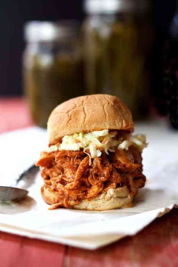 Sweet and Spicy Barbecue Chicken Sliders - Straight-on shot of sandwich with coleslaw on white paper with jars of pickles in the background