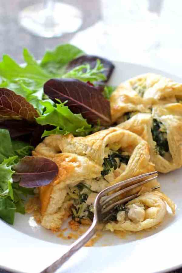 Chicken Spinach and Artichoke Puff Pastry Parcels - On white plate, cut into, ready to be eaten