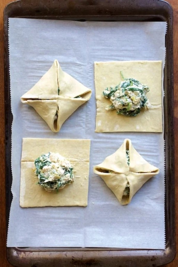 Four parcels on parchment paper-lined baking sheet with filling--two folded, two not yet folded before baking