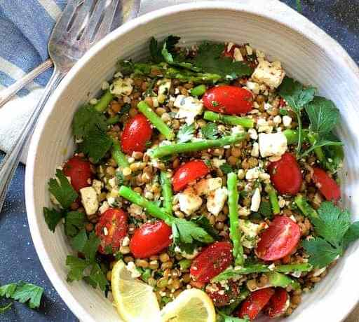 Lentil, asparagus and tomato salad with parsley, feta cheese and lemon slices in a white bowl.