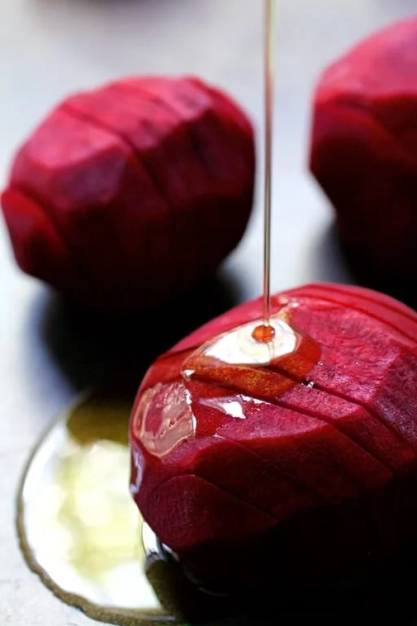 Roasted Hasselback Beets with Dill Dressing - Raw hasselbacked beets being drizzled with olive oil