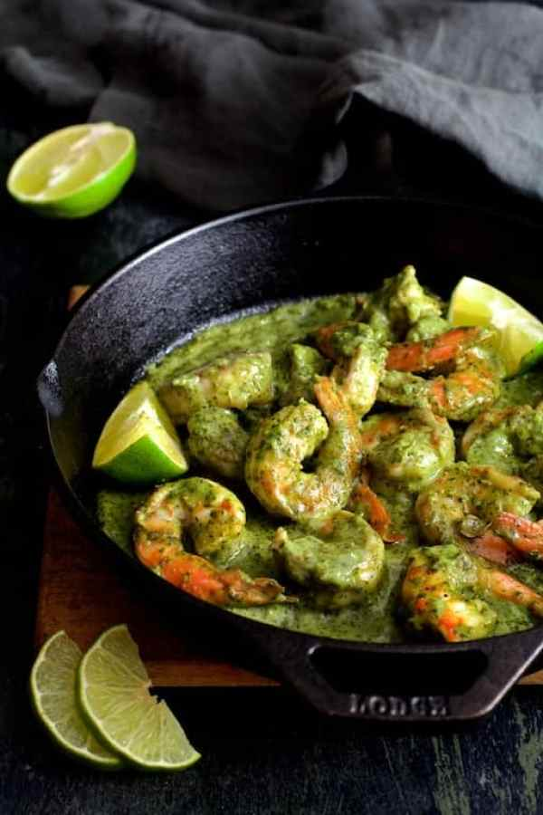 Shrimp in Avocado Butter - Hero shot of dish in cast iron skillet garnished with lime wedges on wood trivet with gray towel over handle