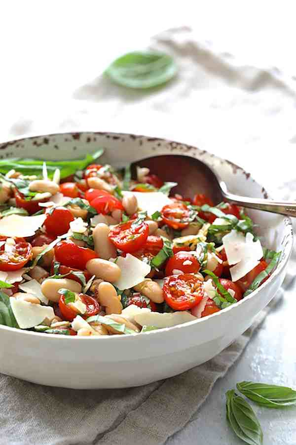 Tuscan Cherry Tomato and White Bean Salad - Straight-on shot of salad in white bowl on beige napkin with serving spoon