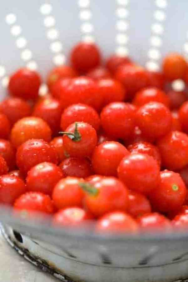 Tuscan Cherry Tomato and White Bean Salad - Close-up photo of freshly washed cherry tomatoes in white antique colander