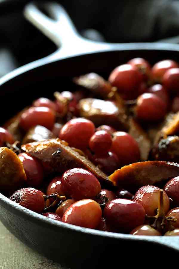 Goat Cheese Polenta with Italian Sausage and Roasted Grapes - Close-up shot of sliced sausages and grapes in cast iron skillet