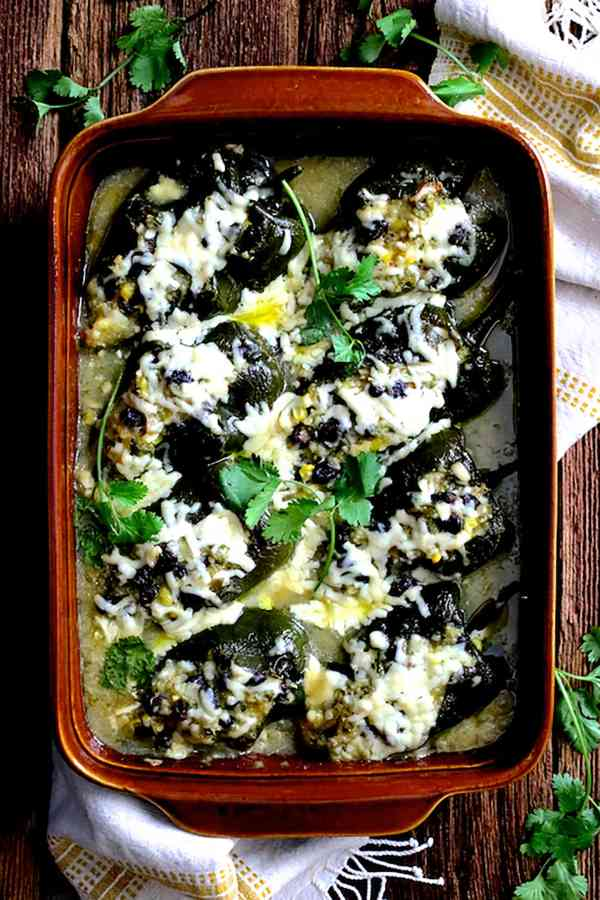Quinoa Corn and Black Bean Stuffed Poblano Peppers - Overhead shot of baked peppers in terra cotta baking dish on wood background garnished with cilantro