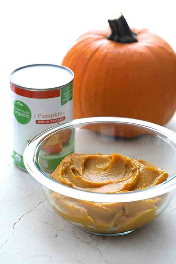 Pumpkin Chipotle and White Cheddar Grits with Bacon-Wrapped Shrimp - Shot of brand's pumpkin in glass bowl with can of pumpkin and whole pumpkin in the background