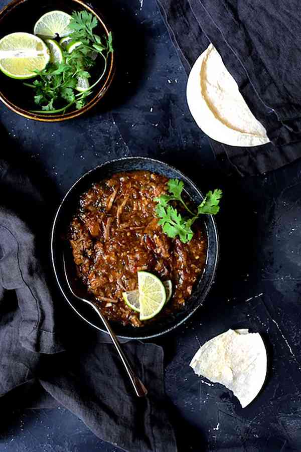 Slow Cooker Colorado Green Chili - Overhead shot of chili in black bowl on black background with lime wedges, cilantro sprigs and corn tortillas