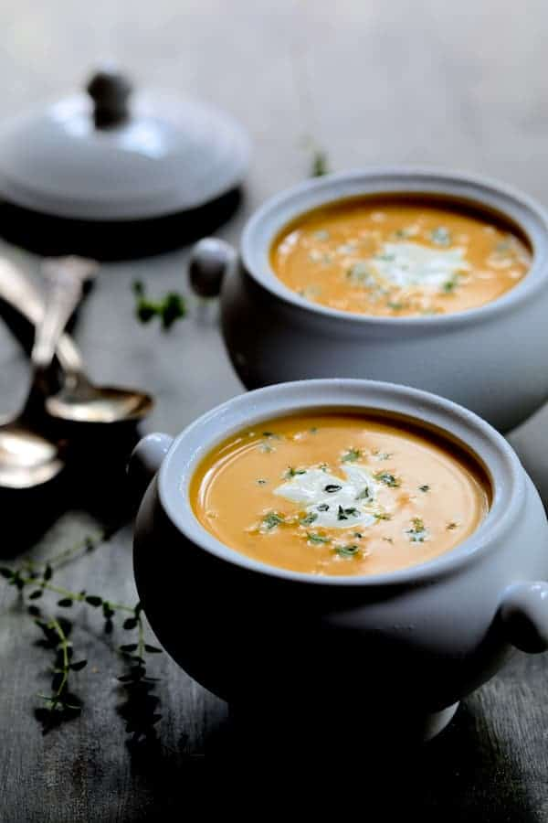 Butternut Squash Soup with Thyme and Taleggio - Photo of two bowls of the soup closer-up garnished with fresh thyme