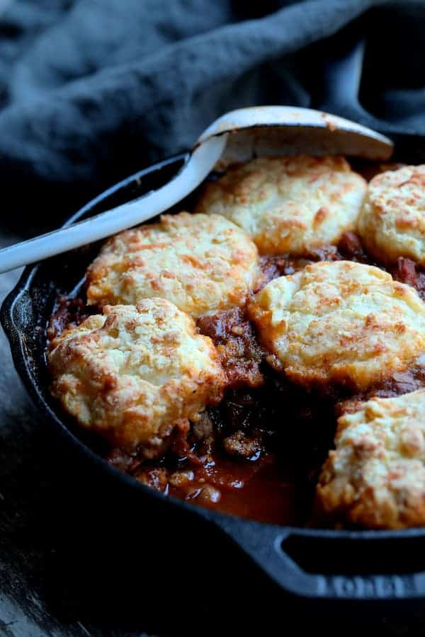 Skillet Turkey Pinto Bean Chili with Pepper Jack Biscuit Topping with a biscuit and some of the chili served from it in cast iron skillet with white metal spoon on the side.