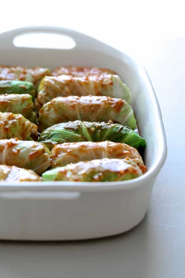 Spicy Asian Pork Cabbage Rolls - Uncooked cabbage rolls in white baking pan with sauce drizzled over the top
