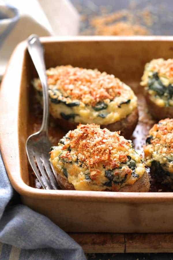 Spinach Parmesan Ranch Twice Baked Potatoes close up shot in clay baking dish with serving fork and blue striped towel