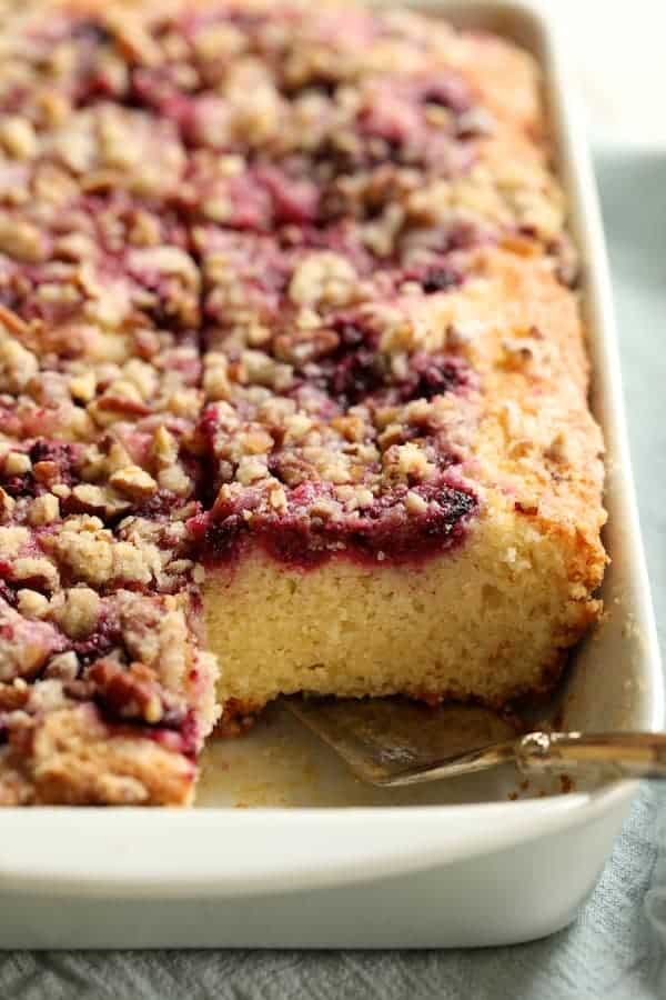 Easy Raspberry Coffee Cake - Cut into pieces looking straight on with silver server about to remove a piece