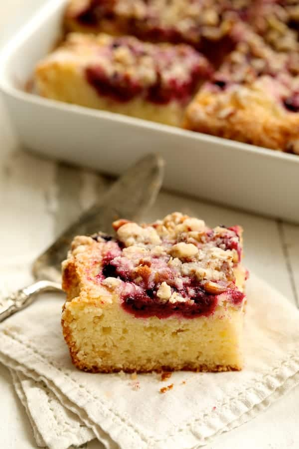 Easy Raspberry Coffee Cake - Piece of cake on napkin with pan of coffee cake in the background