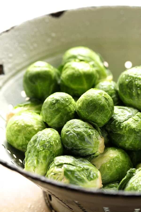 Sriracha Sweet Chili Roasted Brussels Sprouts - Raw washed Brussels sprouts in white colander