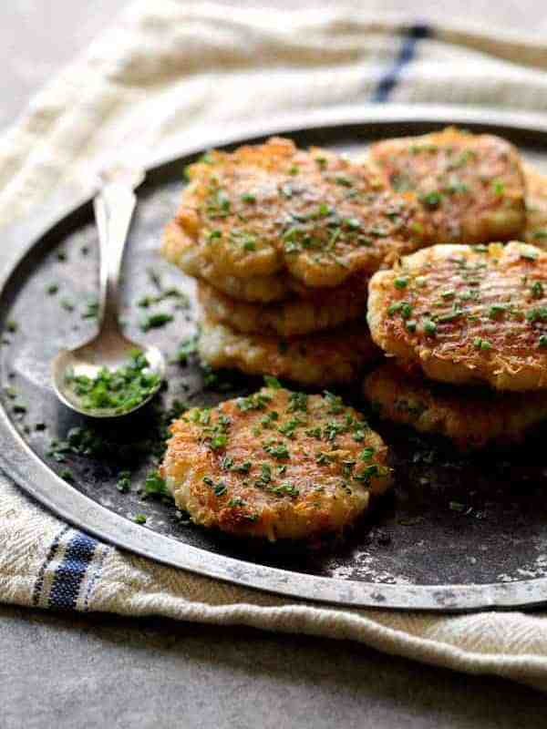 Parmesan Crusted Smashed Turnips - Stacked on metal tray and sprinkled with chives