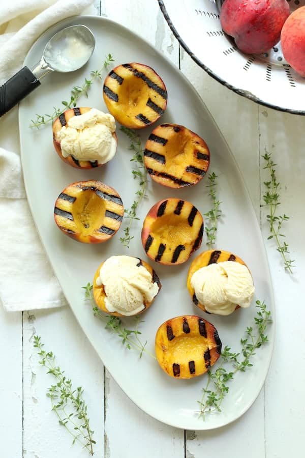 Grilled Peaches with Vanilla Ice Cream and Honey Balsamic Drizzle - Overhead shot of grilled peaches, some with ice cream