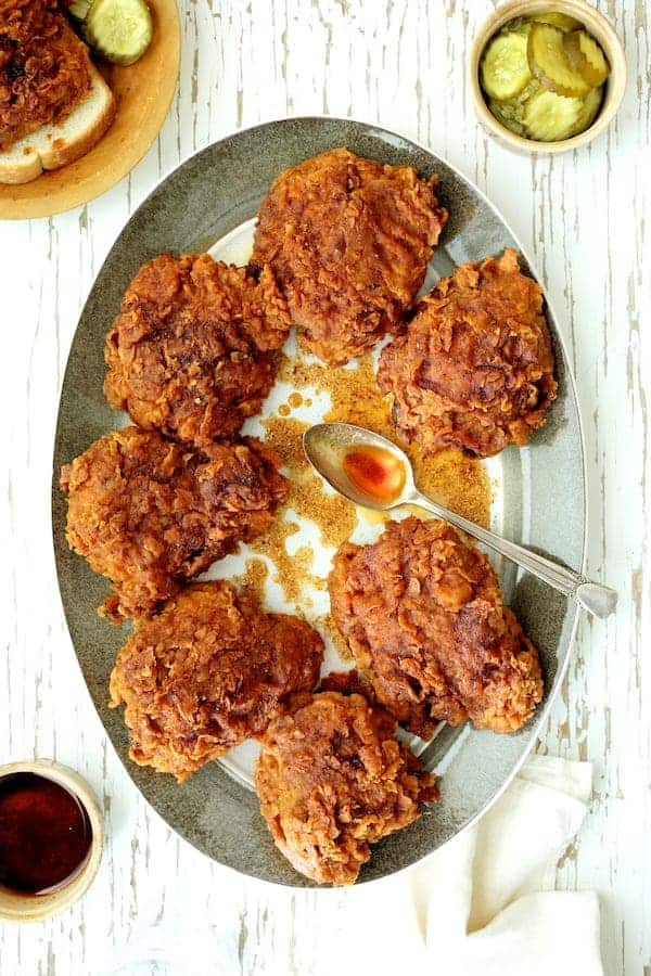 Nashville Style Hot Fried Chicken Hero Shot - Chicken on gray rimmed plate drizzled with hot sauce