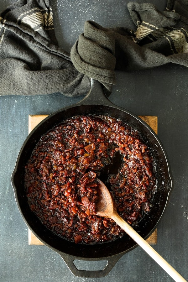 Grilled Burgers with Bacon Tomato Jam and Smoked Gouda - Overhead shot of bacon jam in cast iron skillet on wood trivet. Handle of skillet wrapped in gray striped kitchen towel
