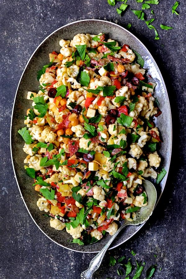 Cauliflower Antipasto Salad - Overhead shot of salad on gray-rimmed platter with decorative serving spoon