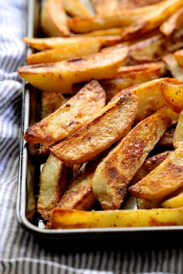 Oven Fries with Spicy Pesto Aioli - Close-up of cooked oven fries on baking sheet