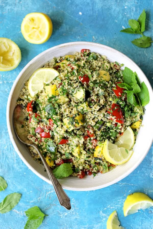 Quinoa Tabbouleh with Grilled Vegetables - Close-up overhead shot of salad in white bowl on blue background
