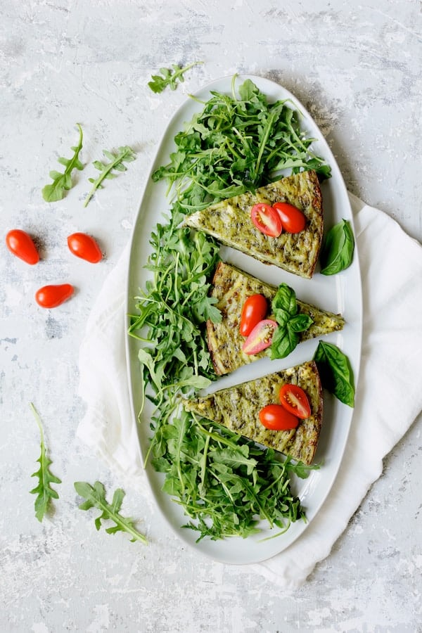 Easy Hash Brown Frittata with Pesto and Goat Cheese - Another overhead shot garnished with tomatoes and arugula