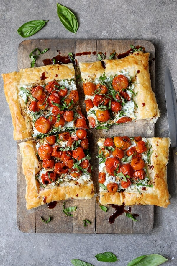 Roasted Cherry Tomato Tart with Herbed Ricottat - Overhead shot of tart on wood cutting board cut into four pieces