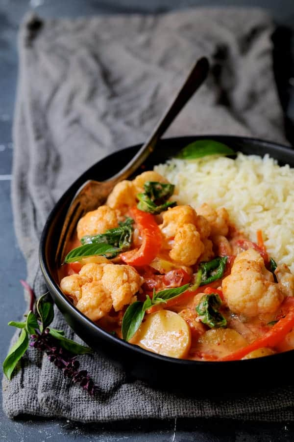Vegan Thai Red Curry with Cauliflower and Potatoes - Side view of curry in black bowl on gray napkin