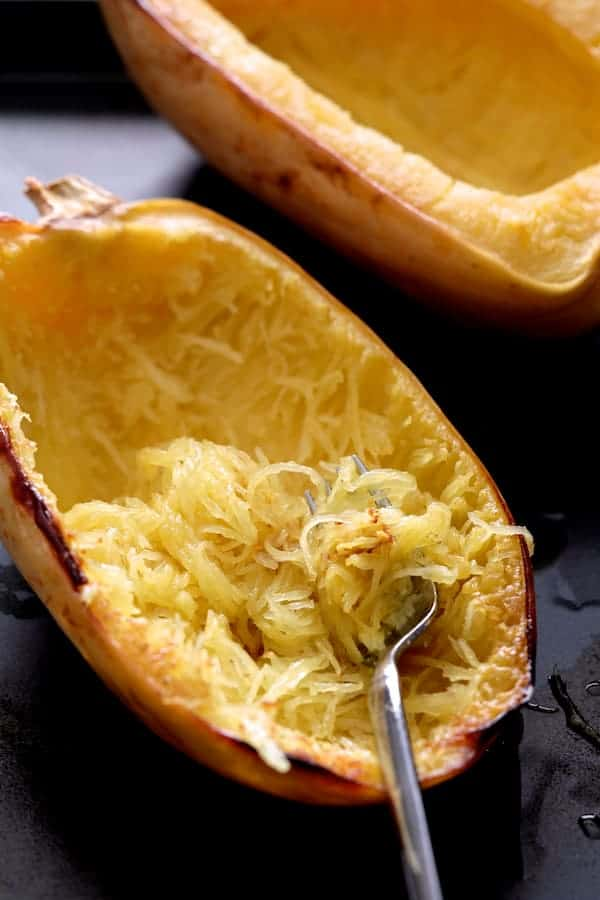 Spaghetti Squash Fries - Cooked spaghetti squash on baking sheet being shredded with a fork