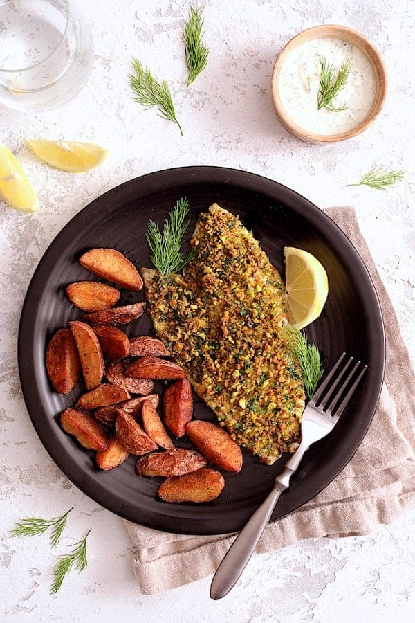 Pistachio-Crusted Fish with Lemon-Dill Aioli - Close-up shot of fish on black plate on white background served with roasted potatoes