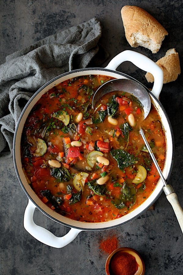 Smoky Spanish Vegetable and White Bean Soup with Kale - Overhead shot of soup in white Dutch ovem with bread and paprika