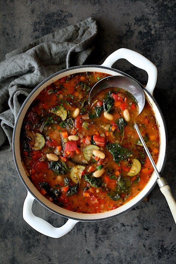 Smoky Spanish Vegetable and White Bean Soup with Kale - Ovehead shot of soup in white cast iron Dutch oven on gray background with gray napkin and ladle