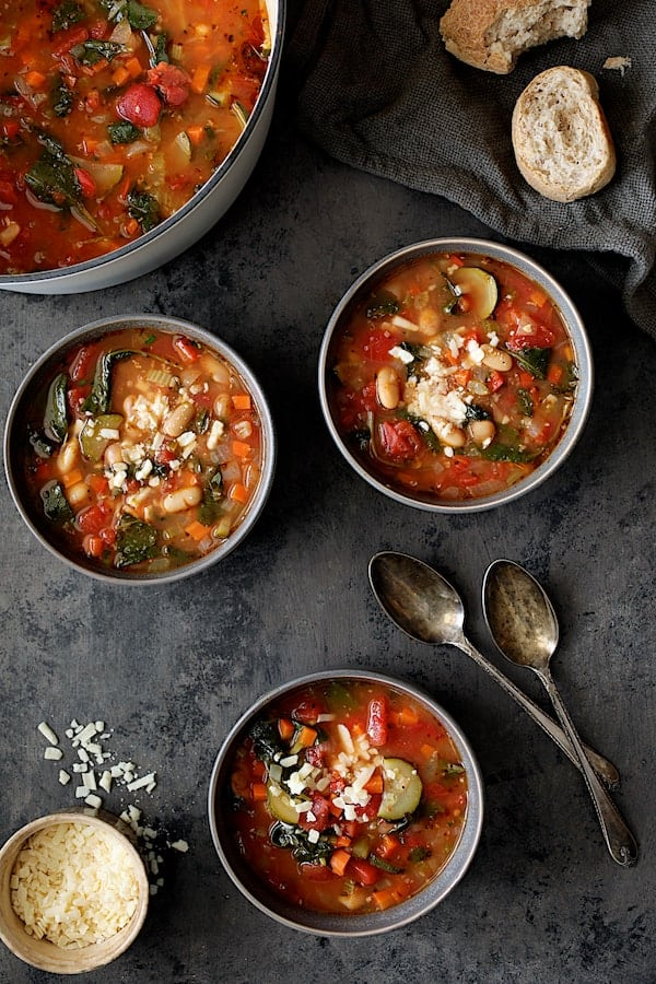 Smoky Spanish Vegetable and White Bean Soup with Kale - Soup dished up into three bowls with broken bread, spoons and gray napkin