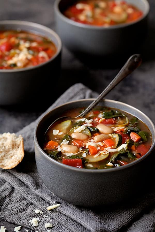 Smoky Spanish Vegetable and White Bean Soup with Kale - Close-up shot of soup in gray bowl on gray napkin