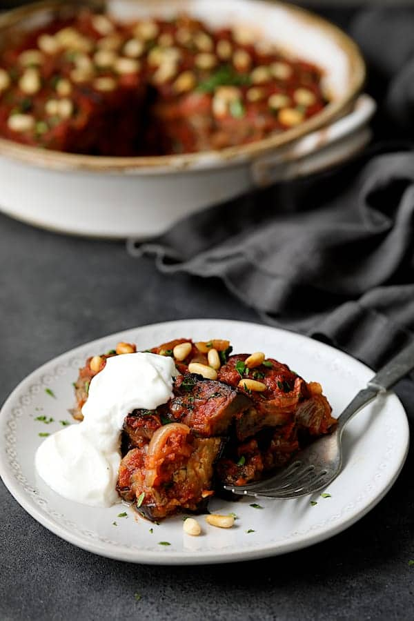 Turkish Eggplant Casserole - Imam Bayildi - Straight-on shot of a piece of the casserole on white plate with a dollop of yogurt
