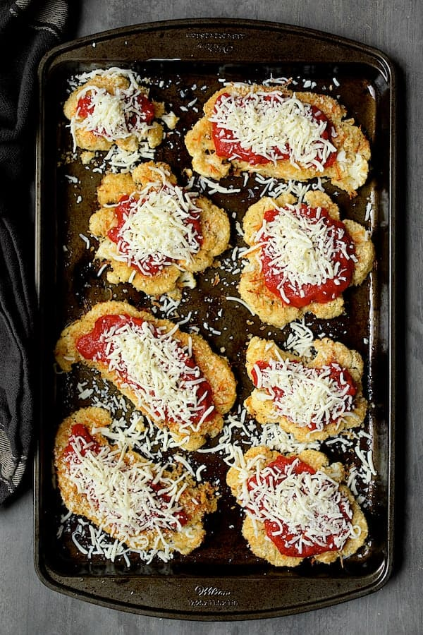 Cauliflower Parmigiana - Overhead shot with sauce and sprinkled with cheese before going back in the oven