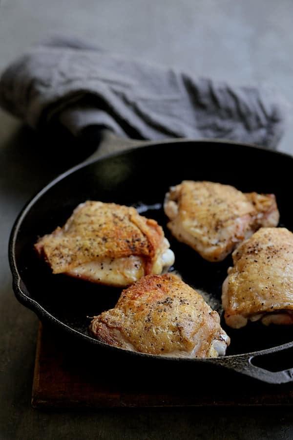 Korean Braised Chicken Thighs - Browned chicken thighs in cast iron skillet