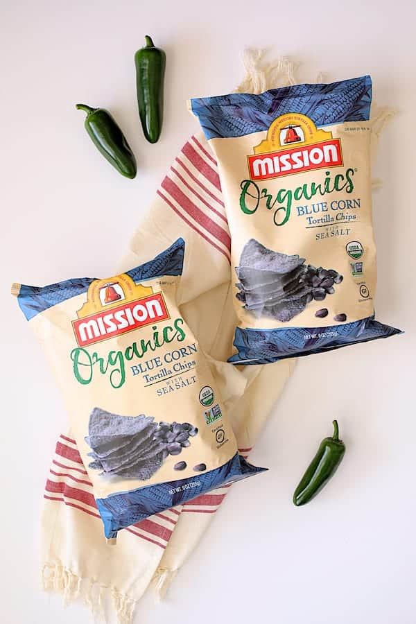 Spinach Artichoke Dip with Fresh Jalapeno - Two bags of Mission chips on white background with red striped towel and jalapenos