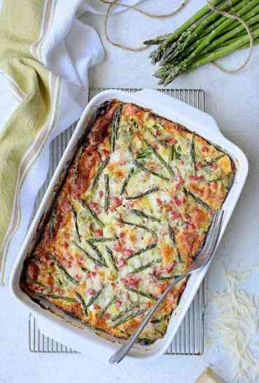 Breakfast Strata with Asparagus, Artichokes, Ham and Gruyere overhead hero shot on white background