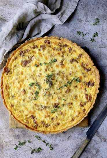 Caramelized Onion and Goat Cheese Tart - Overhead hero shot of tart on gray background