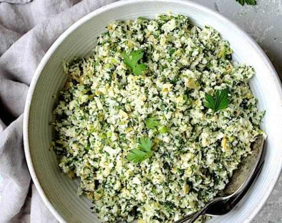 Cauliflower Artichoke Tabbouleh - Overhead hero shot in white bowl on light gray background with light gray napkin
